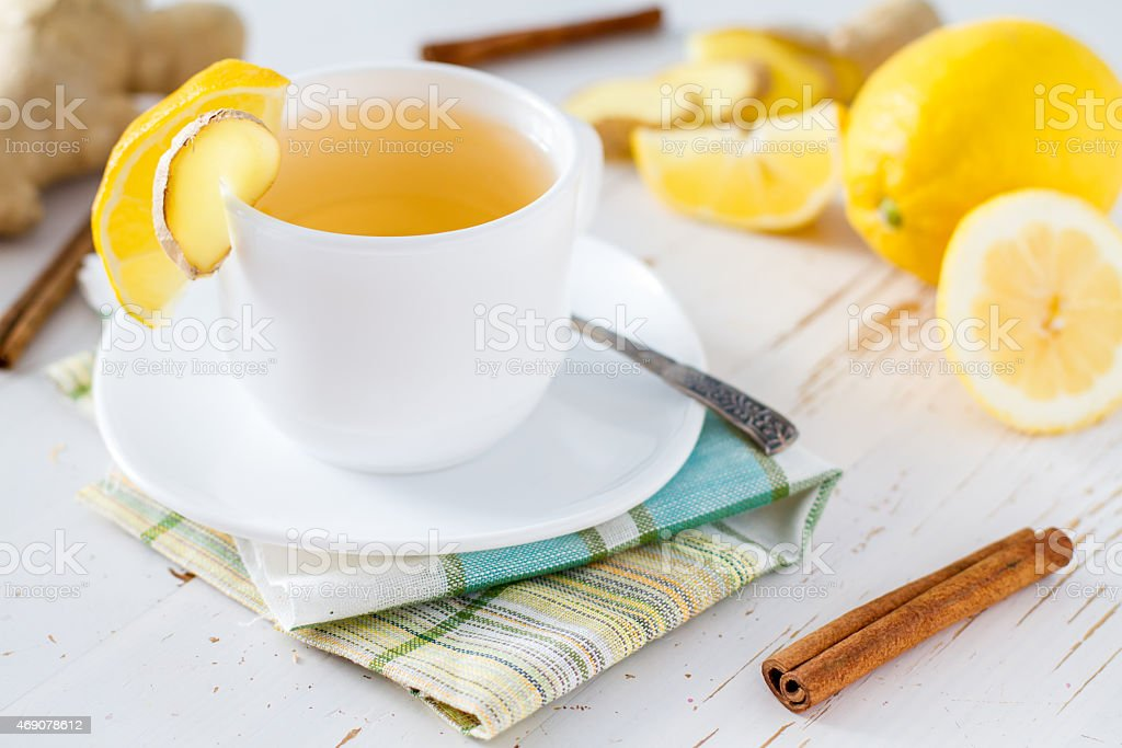 Tea in white cup with ginger, lemon, cinnamon and honey stock photo