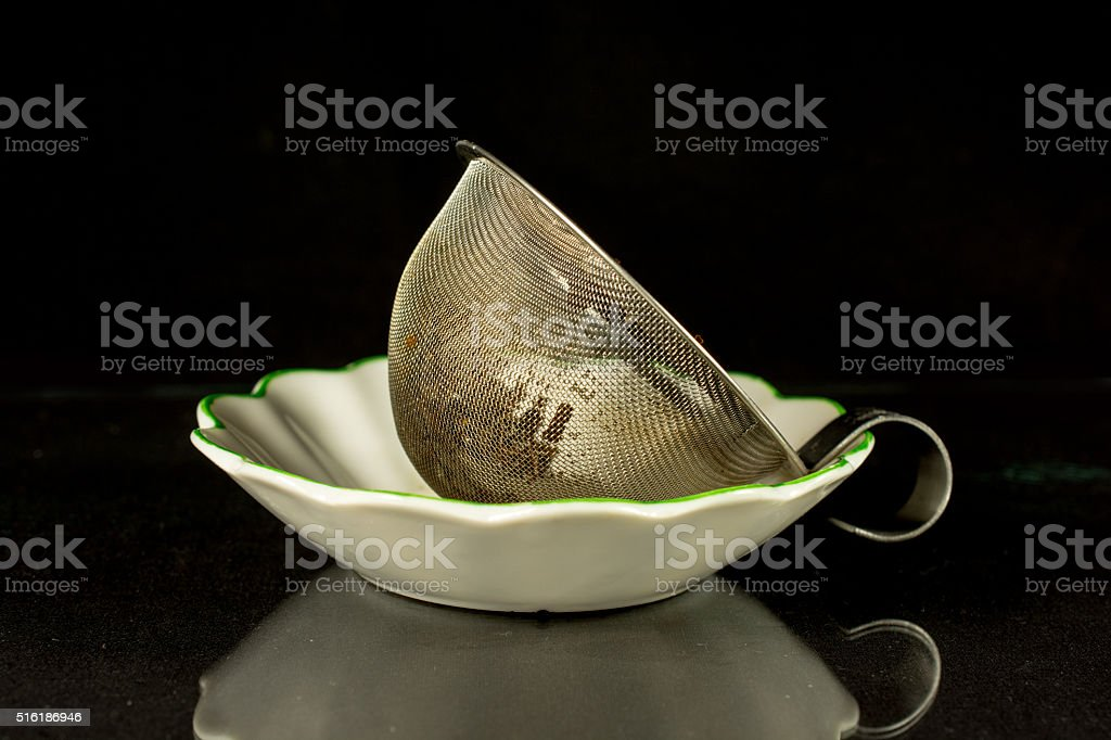 Tea infuser just used on black background stock photo