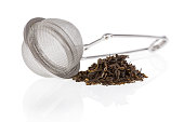 Tea infuser with Green Tea leaves isolated on a white