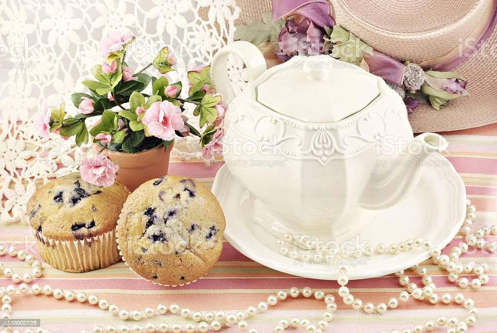 Tea kettle, muffins, and pink flower with pearls stock photo