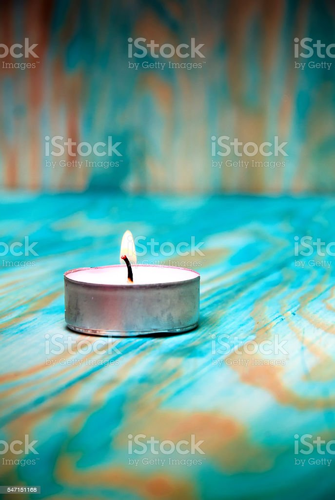 Tea light candle on a blue wooden textured background stock photo