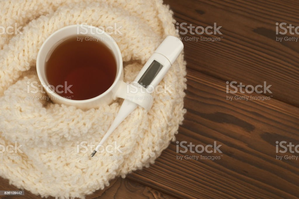 A tea mug wrapped in a soft fluffy knitted scarf, a thermometer on a wooden background - the concept of seasonal autumn diseases, colds, flu treatment stock photo
