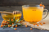Tea of sea-buckthorn berries with a sprig on sackcloth