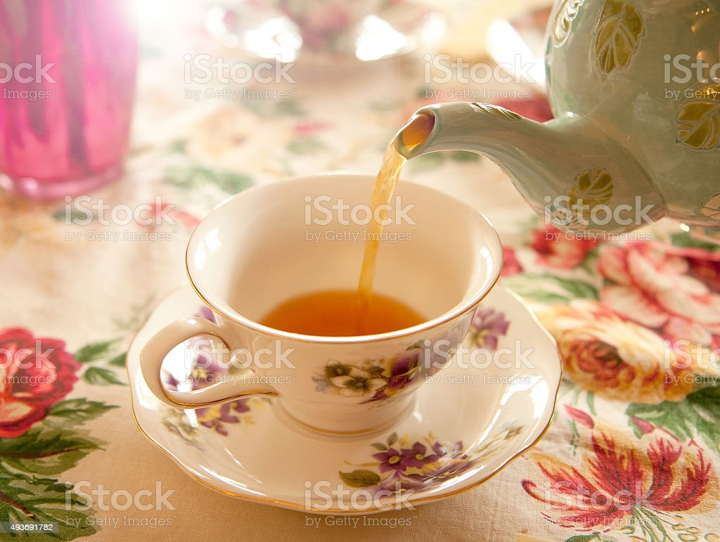 Tea party - Pouring tea into a tea cup stock photo