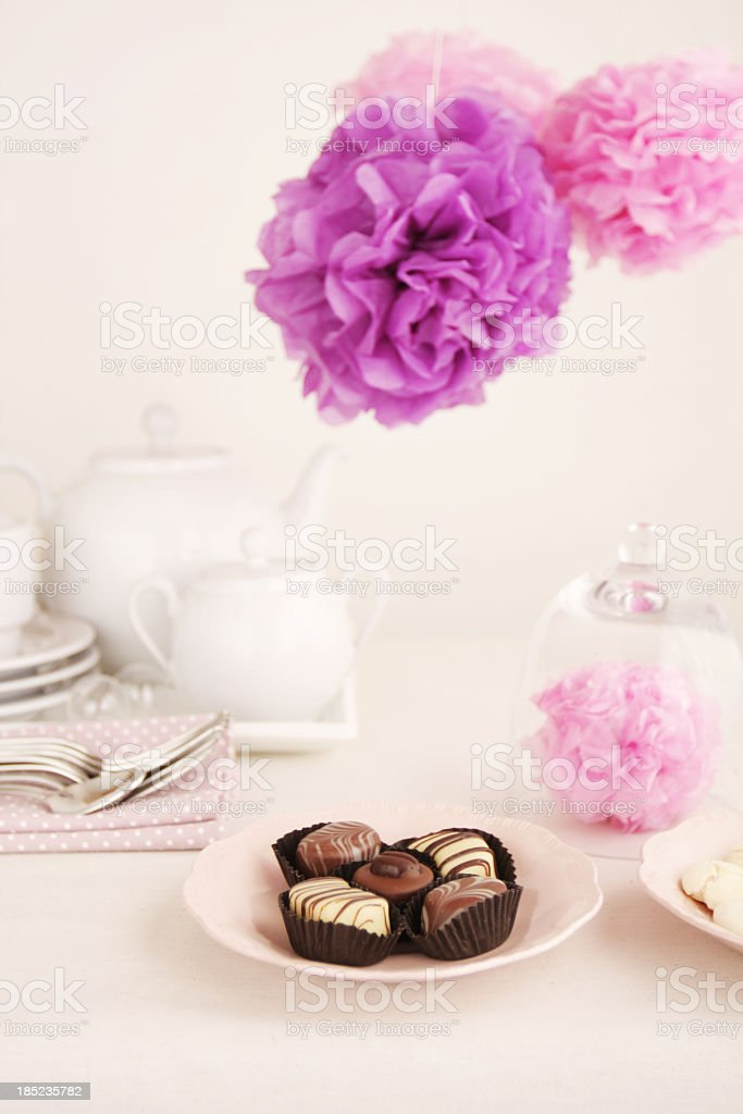 Tea party table with chocolates and pink paper pom pons royalty-free stock photo