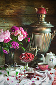 Tea Party with samovar, raspberry and jam in rustic style