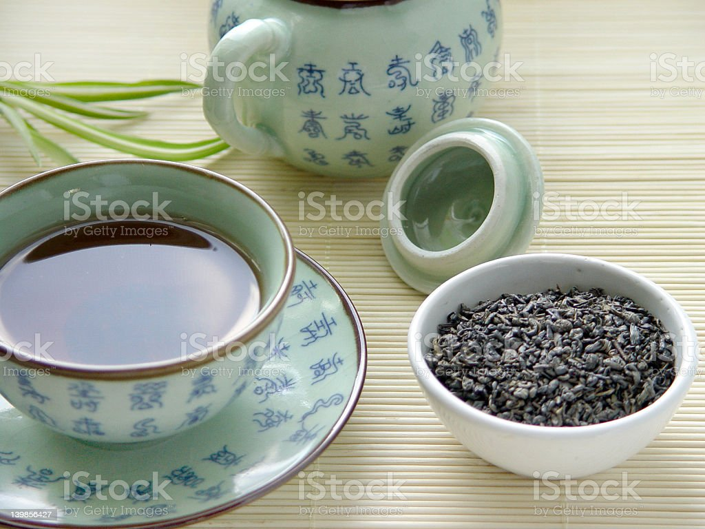 Tea pot and cup of green tea on bamboo table royalty-free stock photo