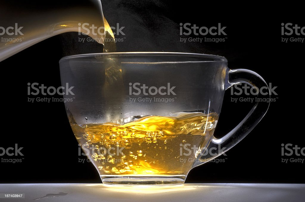 Tea pouring from a white china pot into glass cup. stock photo