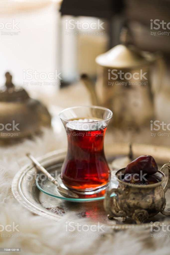 Tea set in oriental style in pear shaped glass with vintage kettle and dates fruit stock photo