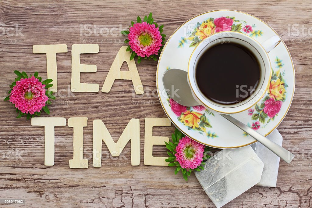 Tea time written with wooden letters, tea and tea bags stock photo