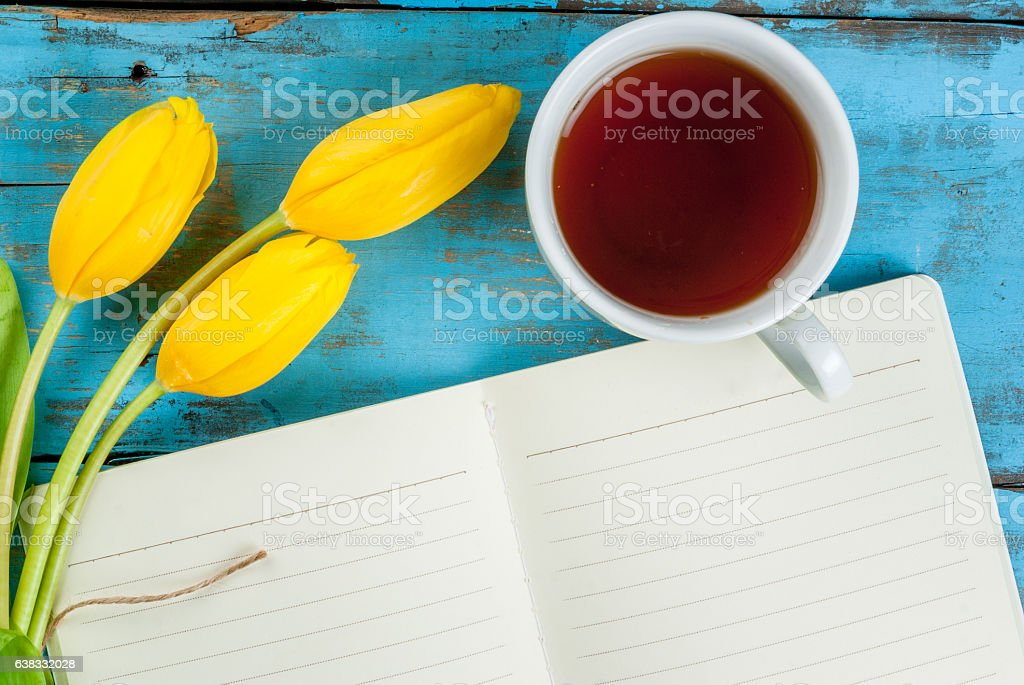 Tea, tulips and notebook on blue table stock photo