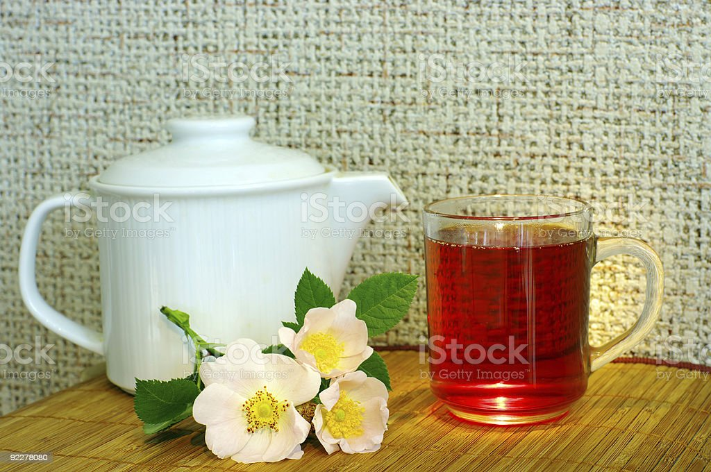 tea with dog-rose flowers and white teapot stock photo