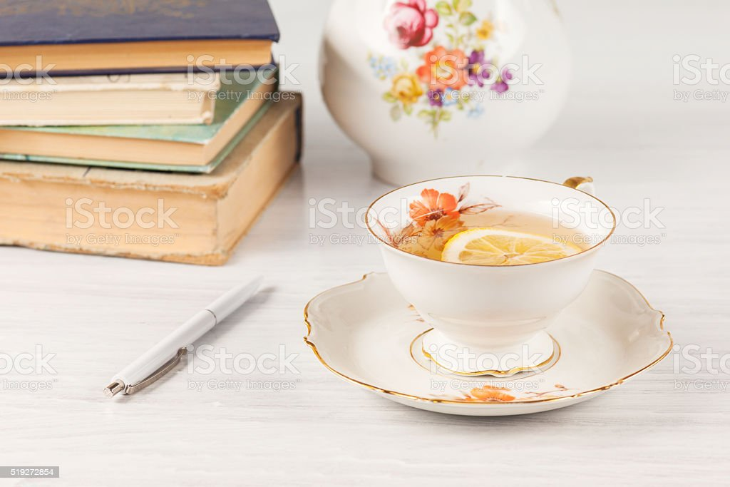 Tea with  lemon and books on the table stock photo