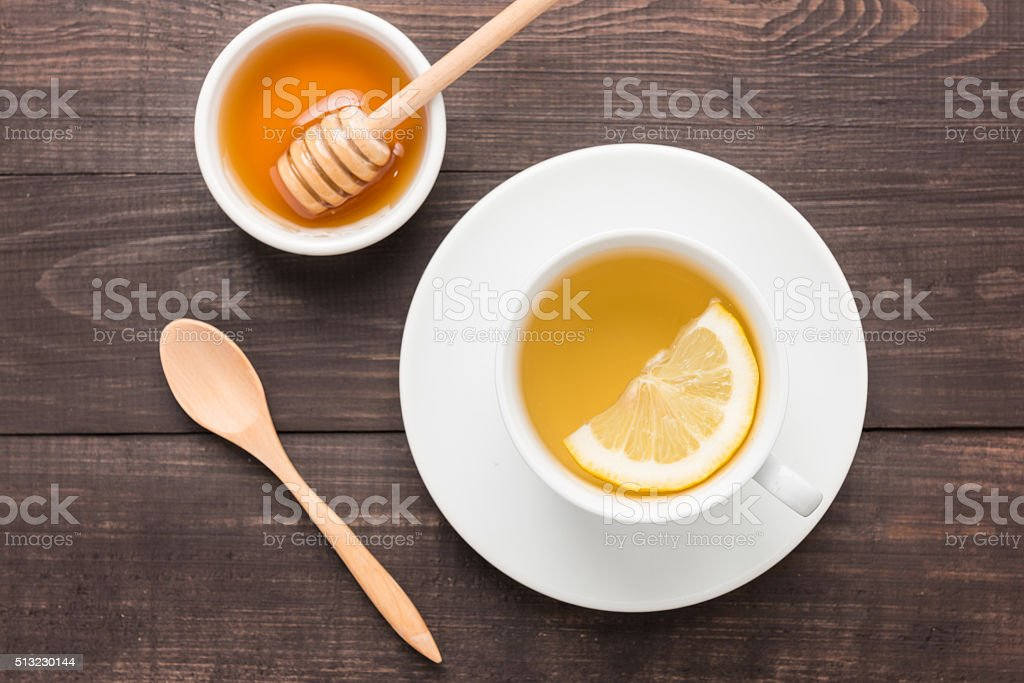 Tea with lemon and honey on the wooden background stock photo