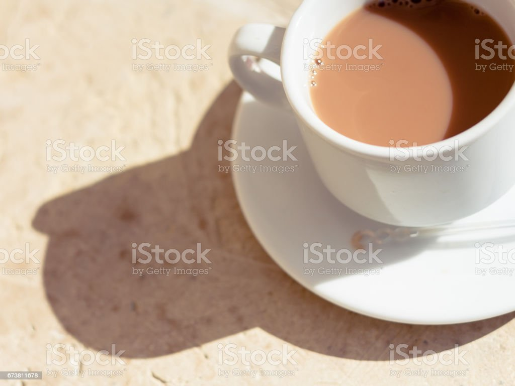 Tea with milk in a white cup in the morning sun with harsh shadows on a textured wood surface. Warm tones. stock photo
