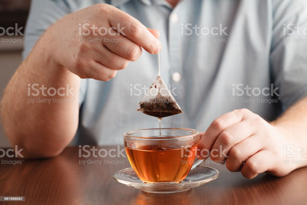 Teabag in the cup with hot water stock photo