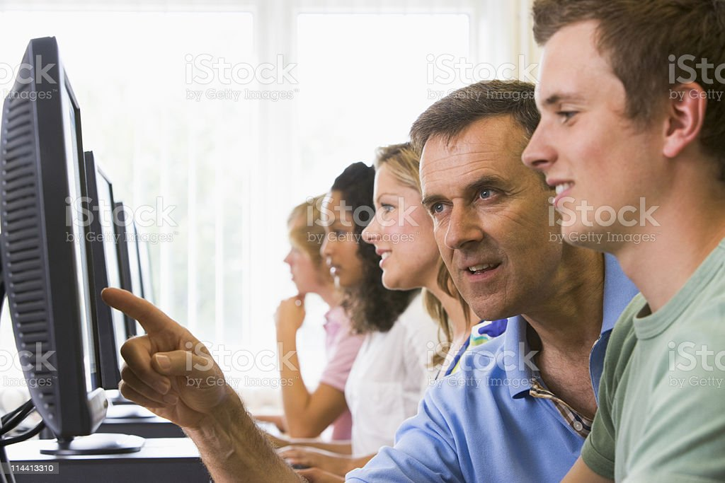 Teacher aiding students while using a computer royalty-free stock photo