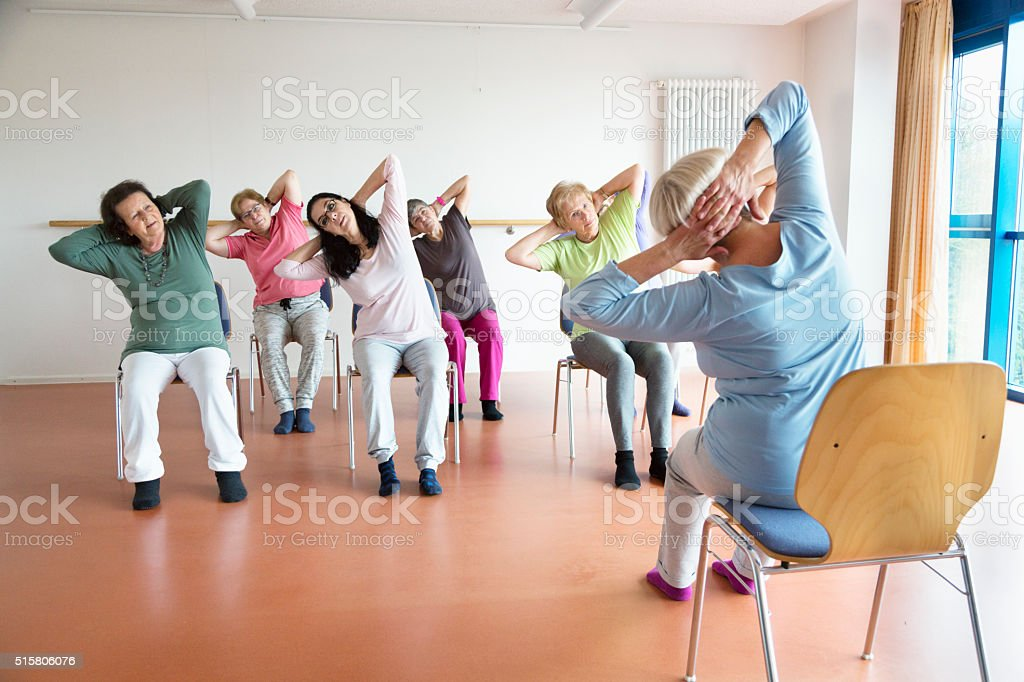 teacher and active senior women yoga class on chairs stock photo