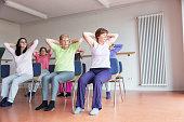 teacher and active senior women yoga class on chairs