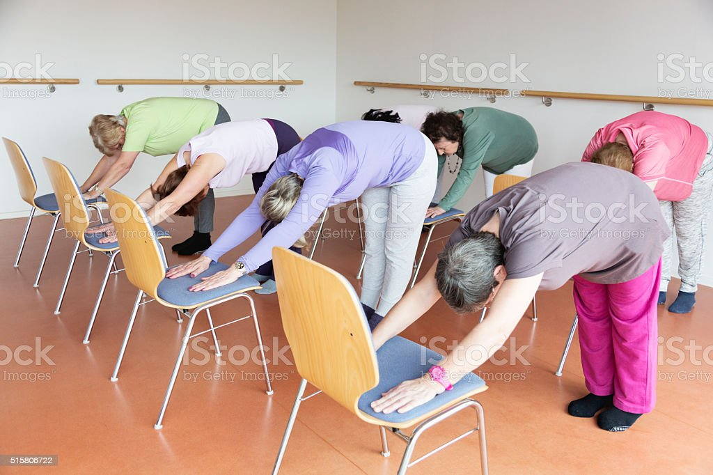 teacher and active senior women yoga class with chairs stock photo