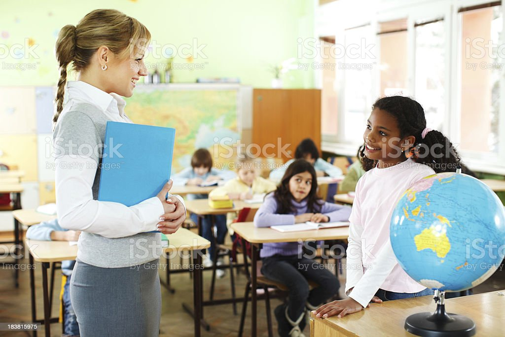 Teacher and girl communicating at the school class. royalty-free stock photo
