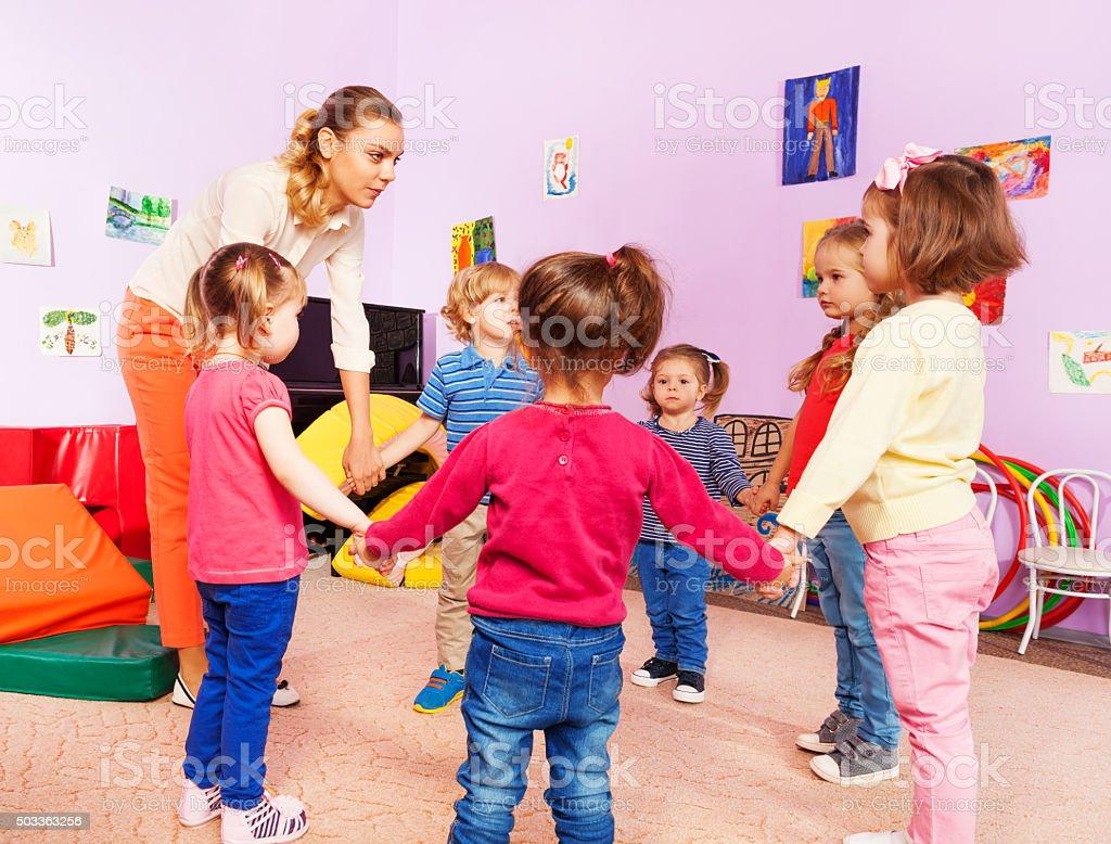 Teacher and group of kids in kindergarten stock photo