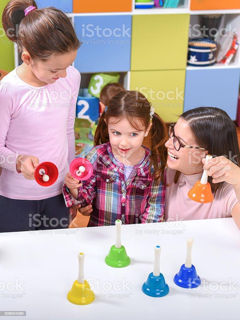 Teacher and Kids - introducing music to preschoolers stock photo