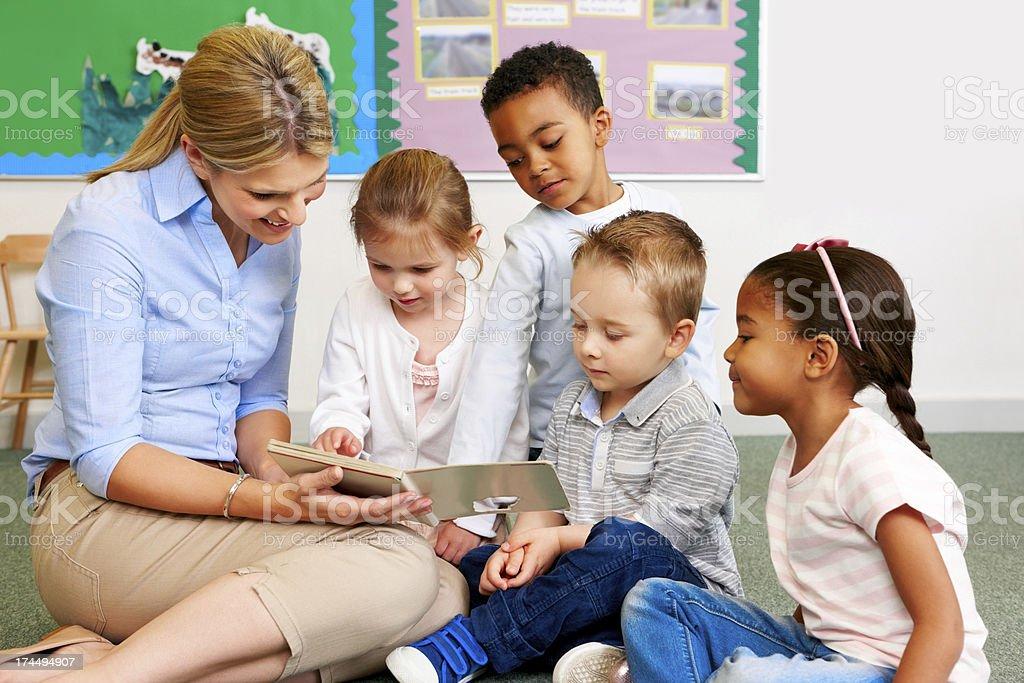Teacher and preschooler reading book stock photo