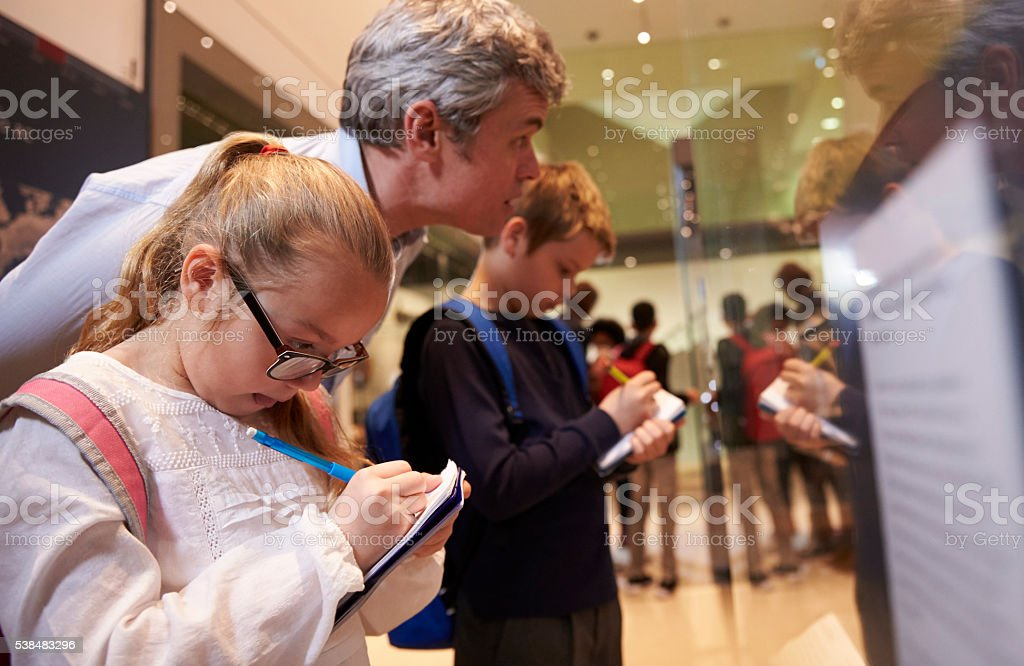 Teacher And Pupils Looking At Artifacts On Display In Museum stock photo