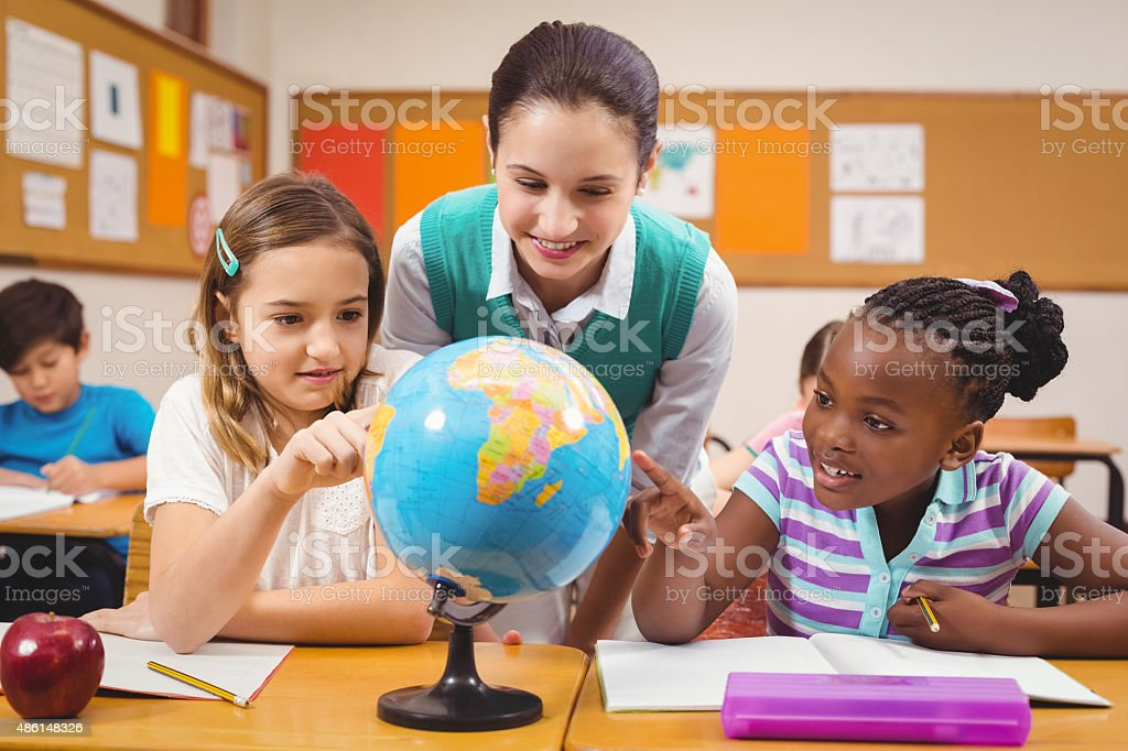 Teacher and pupils looking at globe stock photo