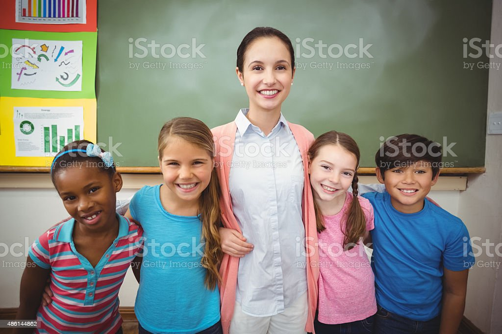 Teacher and pupils smiling in classroom stock photo