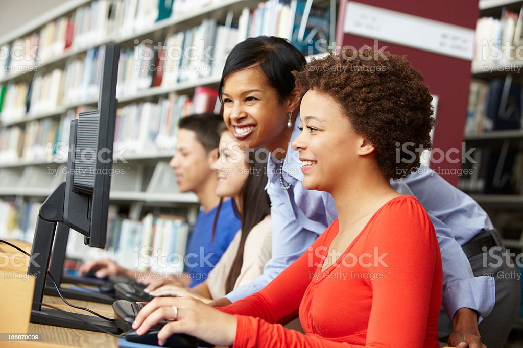 teacher and pupils working on computers royalty-free stock photo