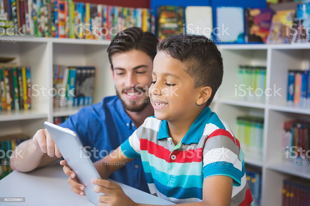 Teacher and school kid using digital table in library stock photo