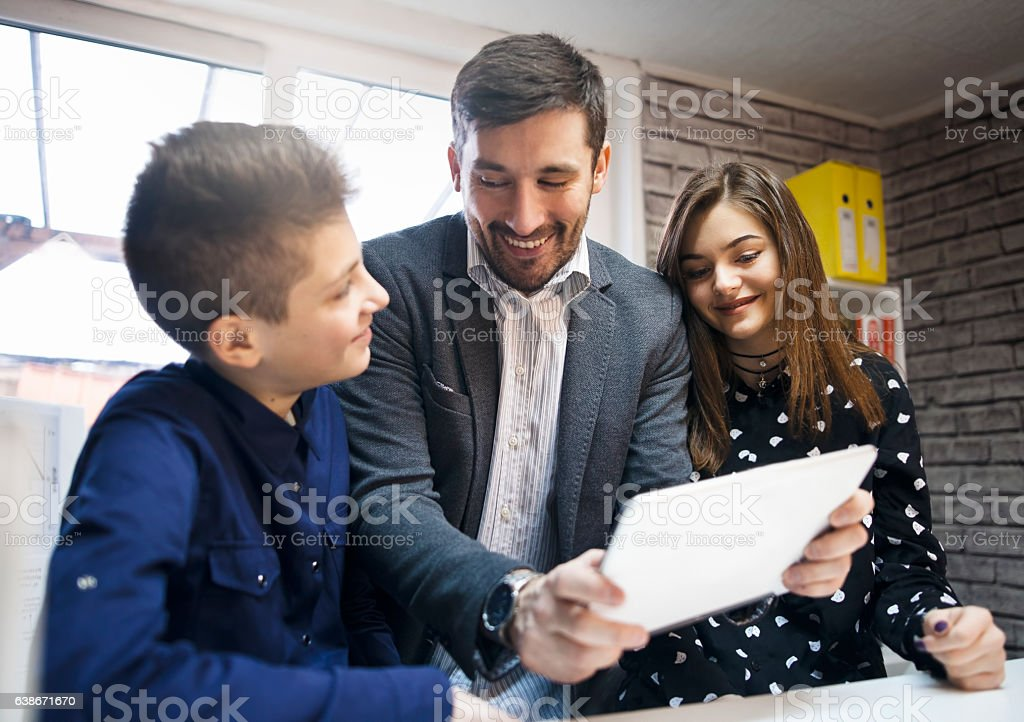Teacher and school kids using digital table stock photo
