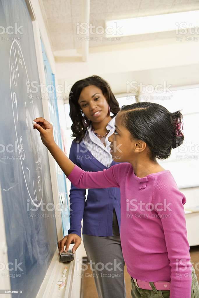 Teacher and Student at Blackboard stock photo
