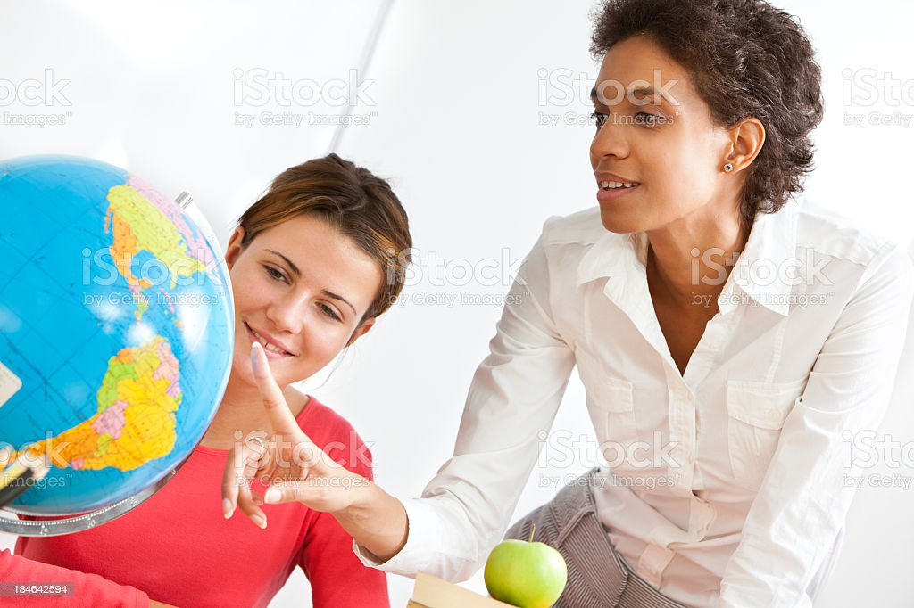Teacher And Student Looking At Globe royalty-free stock photo