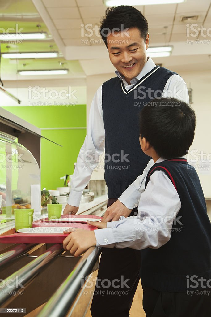 Teacher and student talking in school cafeteria royalty-free stock photo