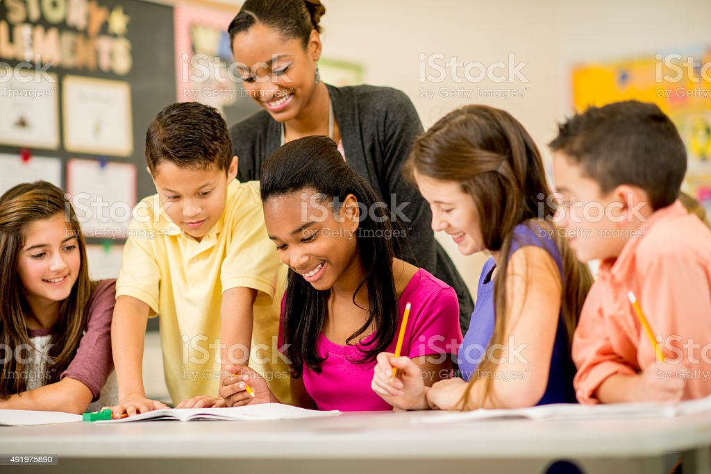 Teacher and Students Doing an Assignment stock photo