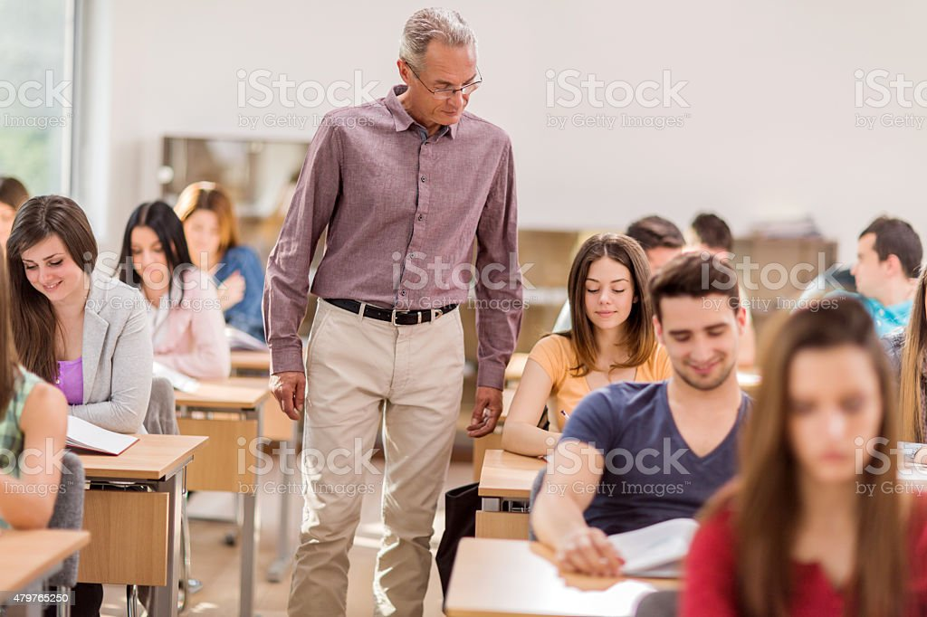 Teacher and students during exam in the classroom. stock photo