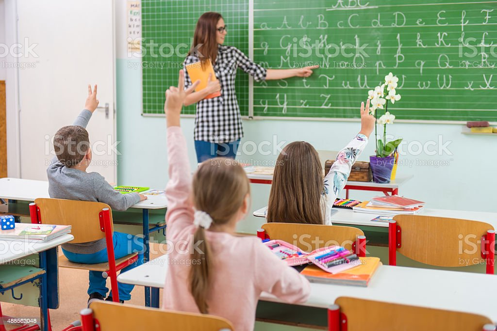 Teacher and students in the classroom: teaching, stock photo