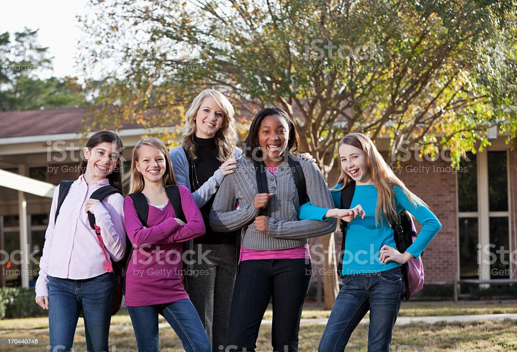 Teacher and students standing outside school stock photo