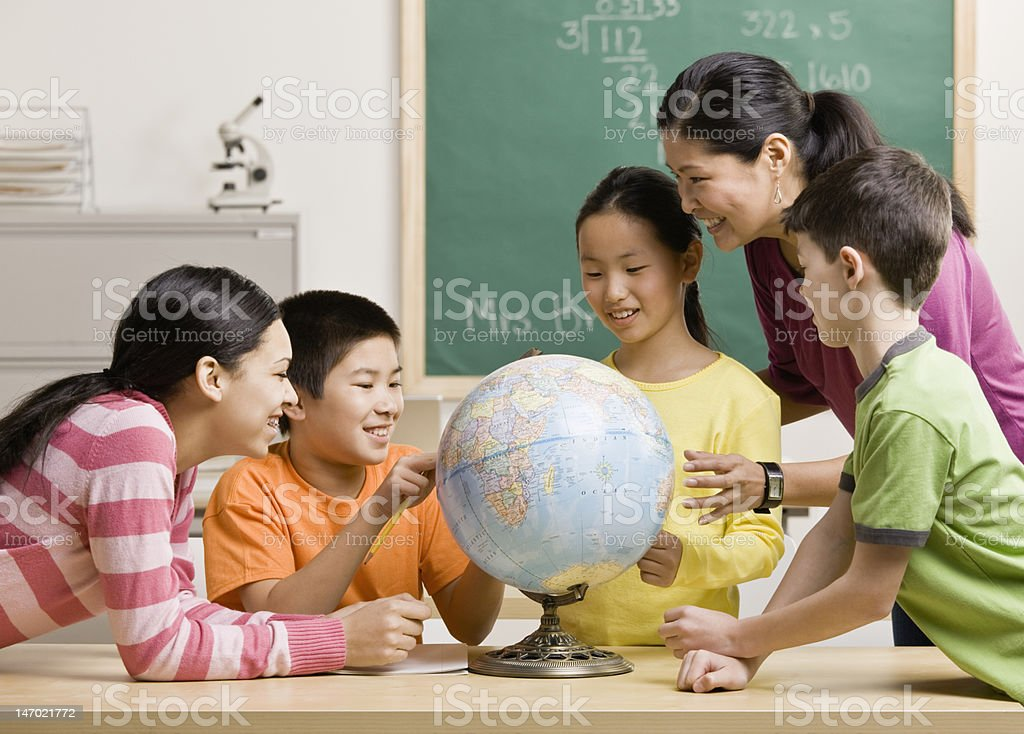 Teacher and students viewing globe in geography classroom stock photo