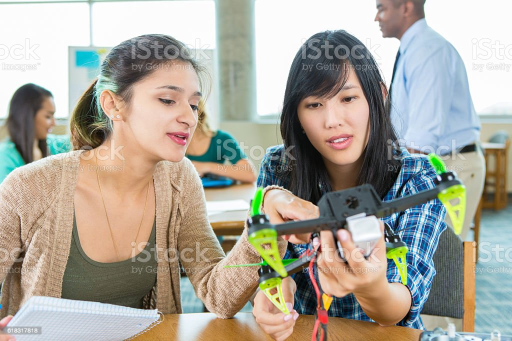 Teacher and students work on drone at STEM school stock photo