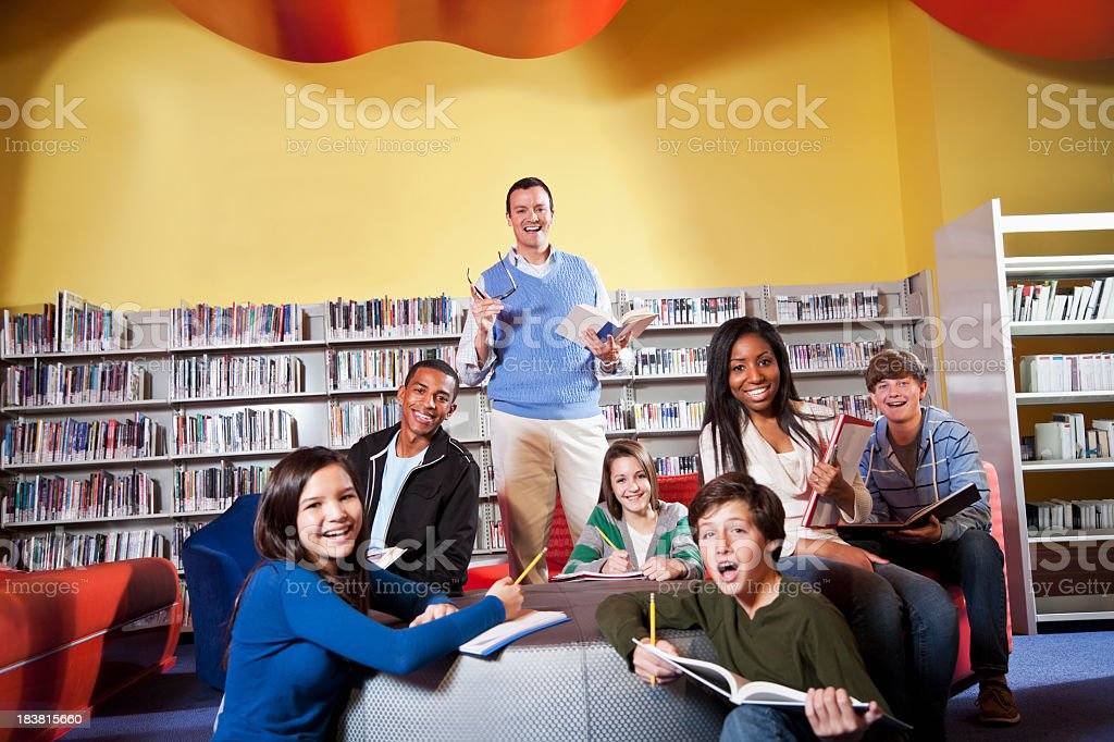 Teacher and teenage students in library royalty-free stock photo