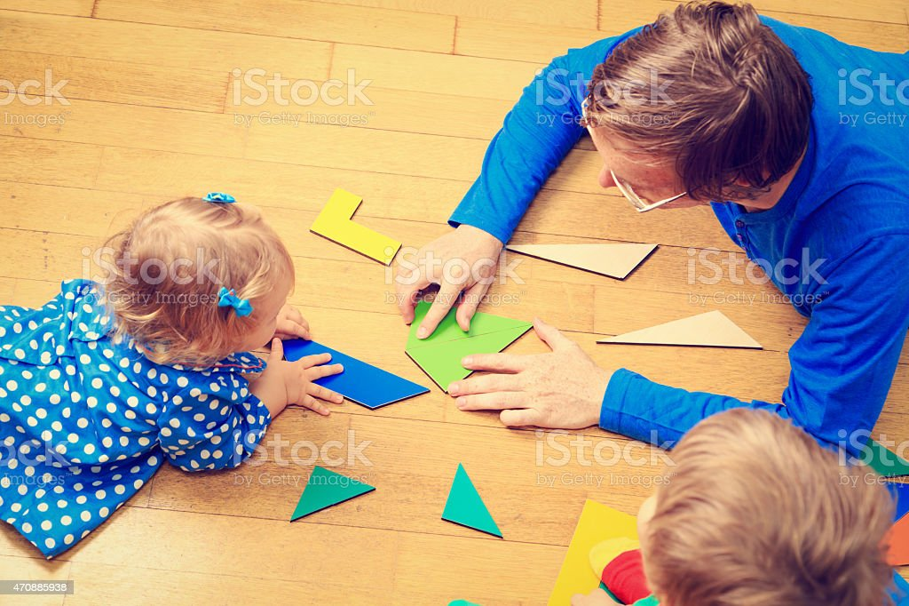 Teacher and the kids laying on a floor playing with shapes stock photo