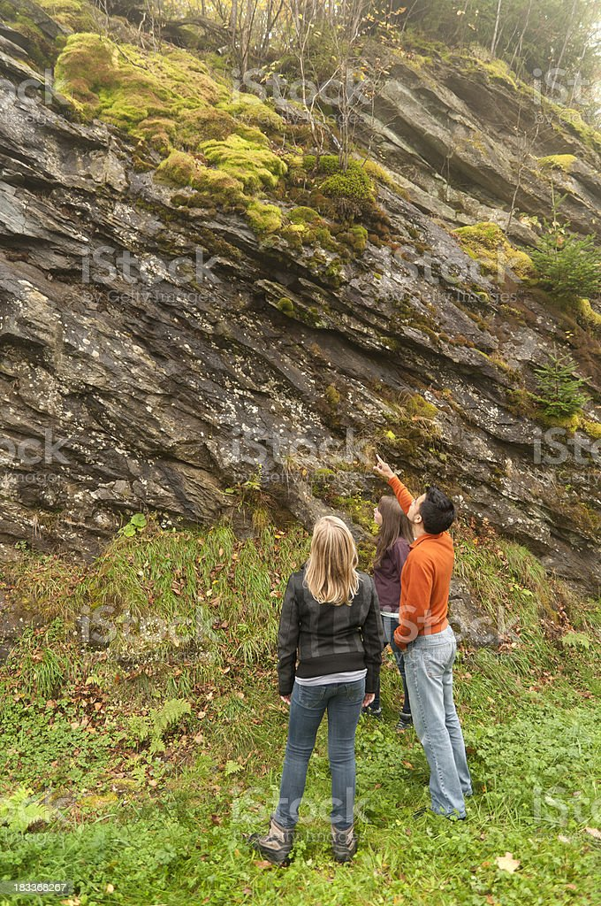 Man teaching two young girls about mosses and lichens