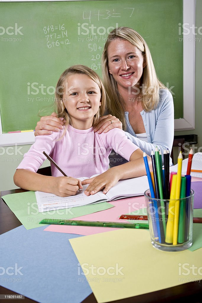 Teacher and young student in class writing royalty-free stock photo