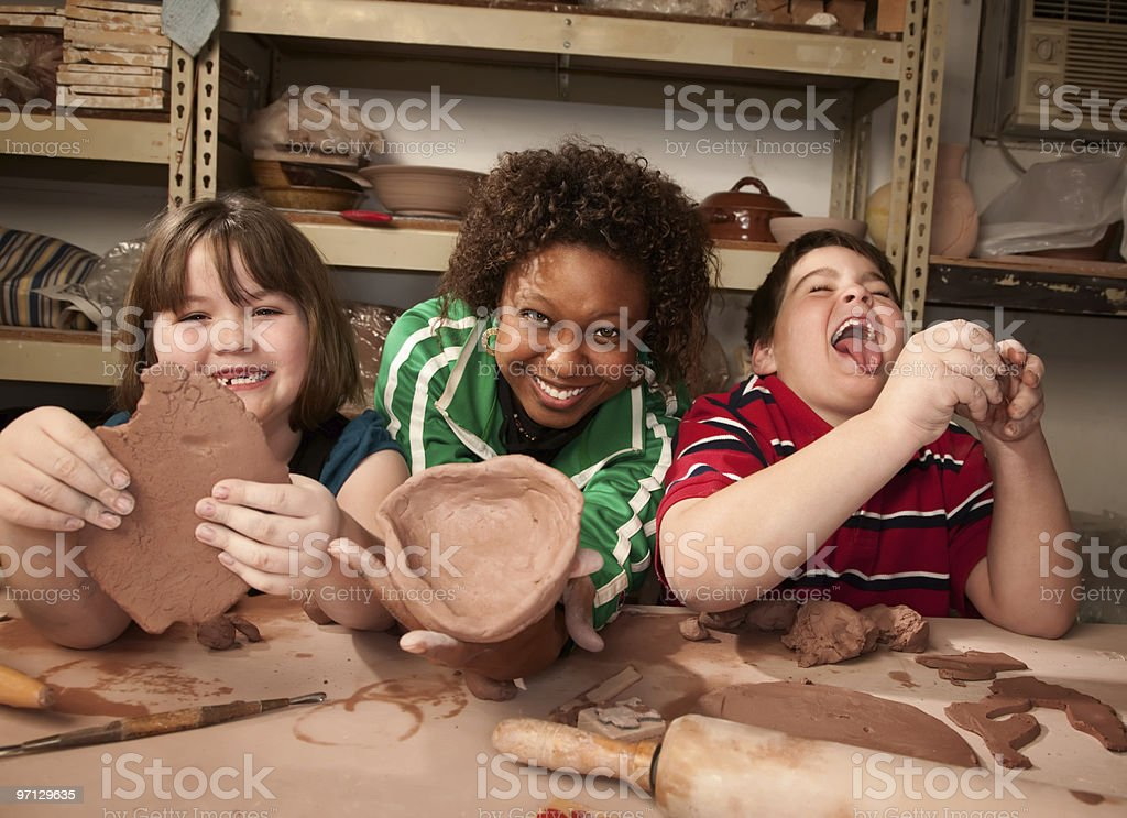 Teacher and young students in clay studio stock photo