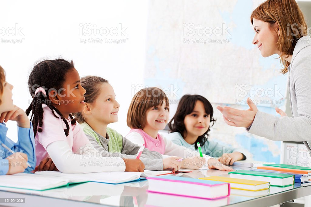 Teacher are explaining to children the task in classroom. royalty-free stock photo