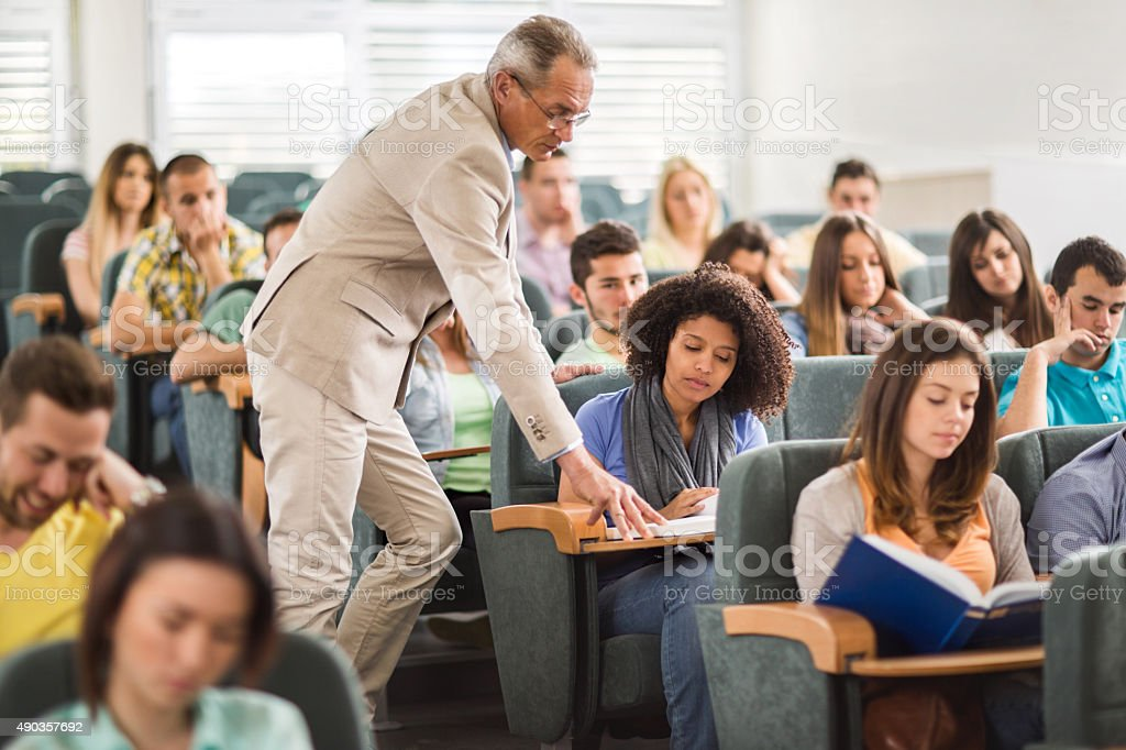 Teacher assisting African American student during lecture in amphitheatre. stock photo